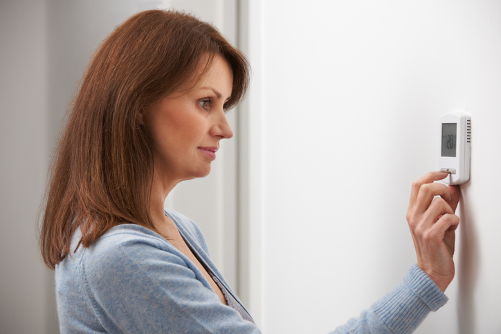 Woman Adjusting Thermostat On Central Heating