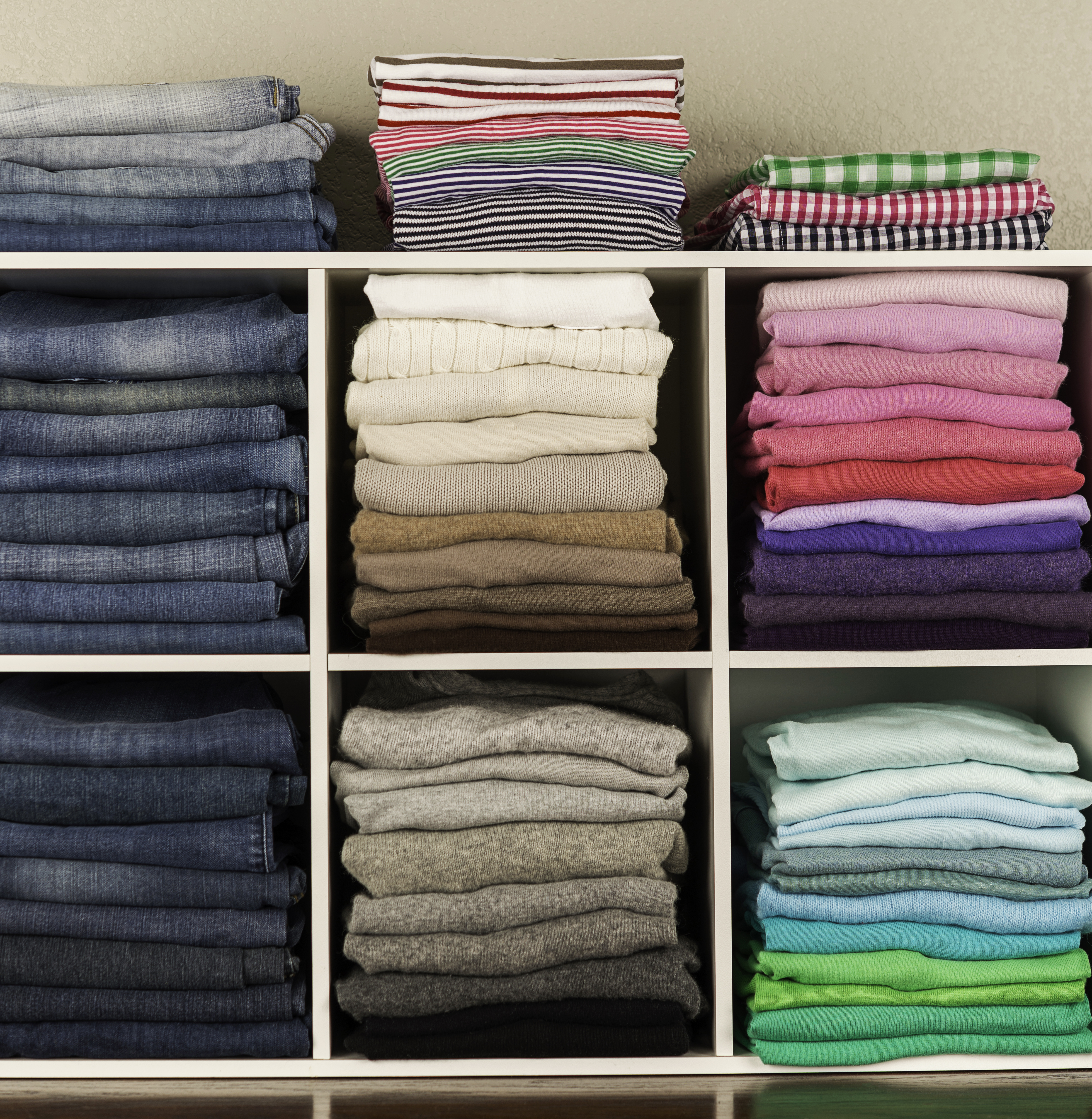 Neatly organized womens clothing in white cubicles