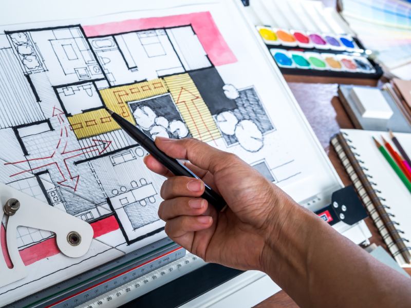 Hand working with architecture hand-drawn sketch on modern creative workspace