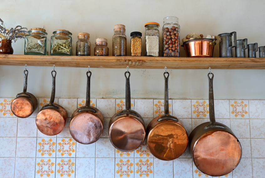 Old saucepans hanging from in a traditional-style kitchen