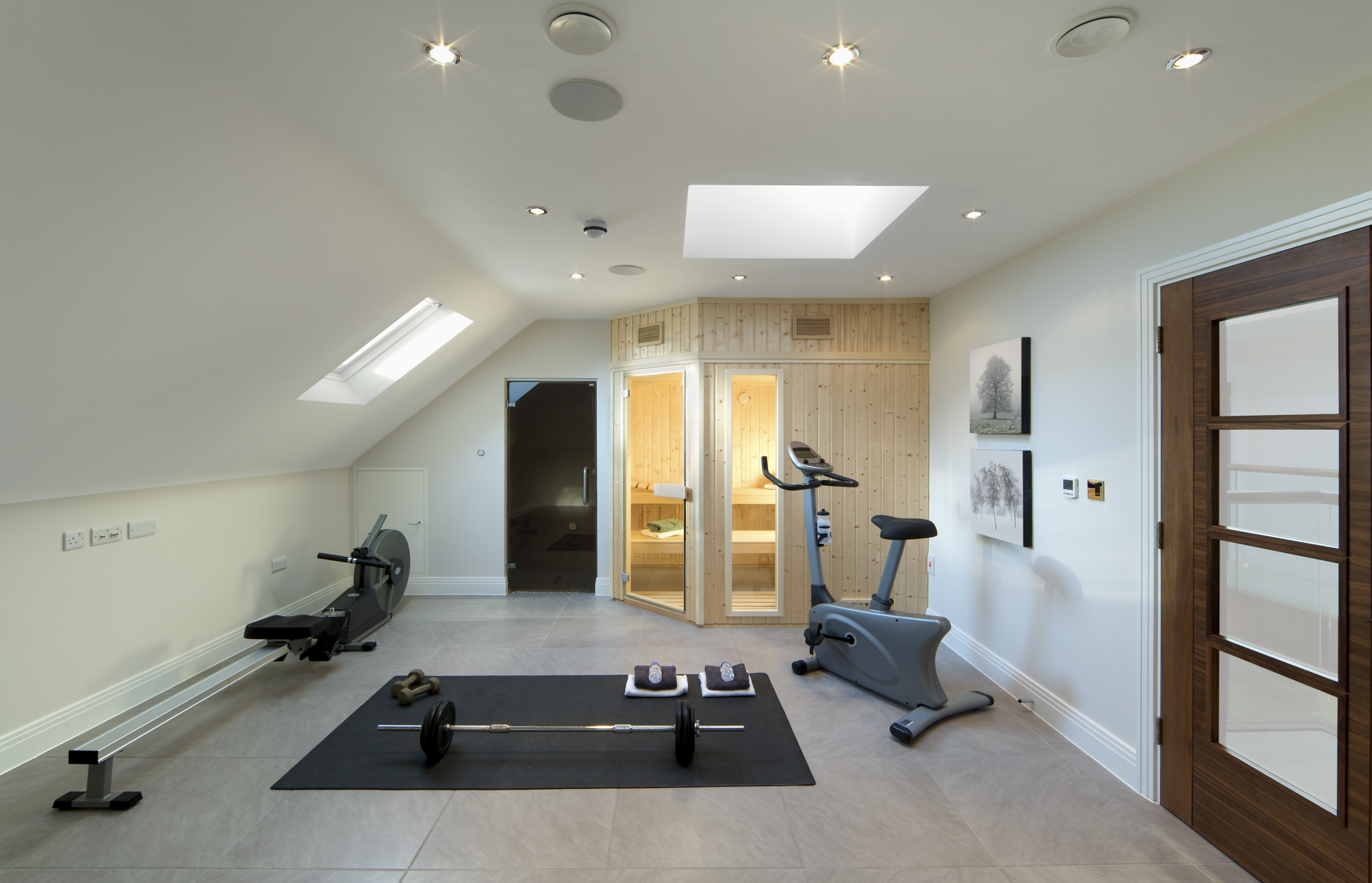 """A gym and sauna room in the loft of a luxury new home. Next to the sauna is a shower cubicle. Equipment includes an exercise bike, rowing machine and some free weights. Natural light is streaming in through two skylight windows. Photographer's own imagery on walls.Please see my other Interior and Architectural images by clicking on the Lightbox link below...A>AA>A"""