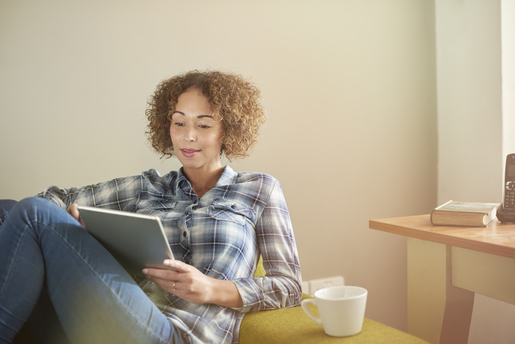 a woman sits on a sofa with her digital tablet and catches up with some streaming entertainment or possible reading an e-book